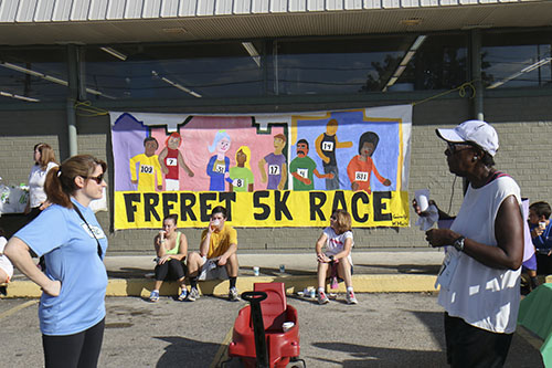 Freret 5K sign, hand painted by students from McMain charter school, hung on the wall of the Junior League of New Orleans' Boomin' Deals Thrift Store. (Zach Brien, UptownMessenger.com)