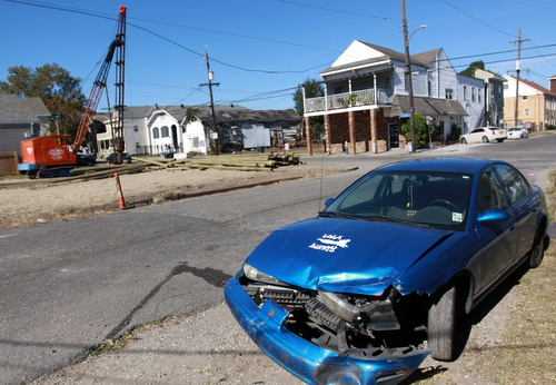 A damaged blue Saturn sits in the 2000 block of Foucher, after a fatally wounded woman was found in a Mercedes that crashed into it. (Robert Morris, UptownMessenger.com)