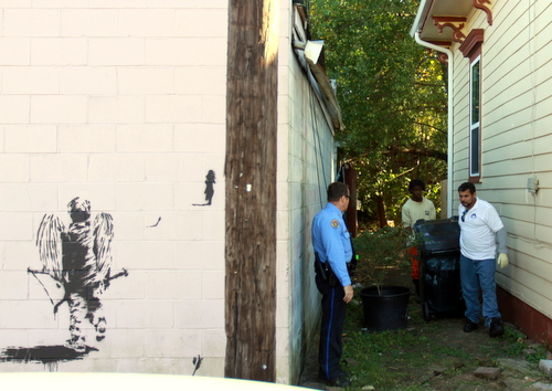 New Orleans police take a trash can into evidence (after the body of a woman found in it was removed) from an alleyway off Danneel Street on Nov. 26. (UptownMessenger.com file photo by Robert Morris)