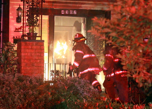 Firefighters enter a house on South Miro to extinguish flames inside. (Robert Morris, UptownMessenger.com)