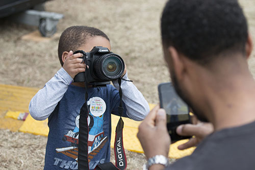 Andre Perry (left) takes his father Robeson's photograph during Mia Borders' performance. Andre seemed like a natural with the camera. (Zach Brien, UptownMessenger.com)