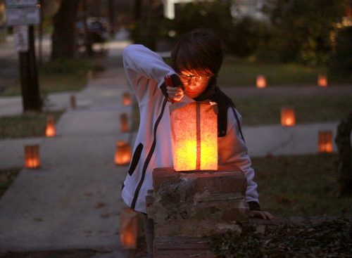 Eli Pirner lights one of several hundred candles on Pine Street on Christmas Eve. (Robert Morris, UptownMessenger.com)