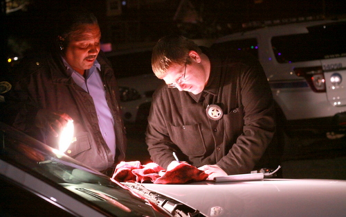 Police officers document a gun recovered during the manhunt near Cadiz and Loyola streets on Sunday, Jan. 4. (Robert Morris, UptownMessenger.com)