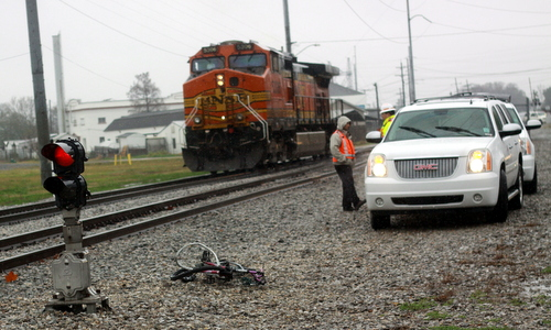 A mangled bicycle sits near a stalled train on Leake Avenue following the discovery of a dead man's body there Wednesday morning. (Robert Morris, UptownMessenger.com)