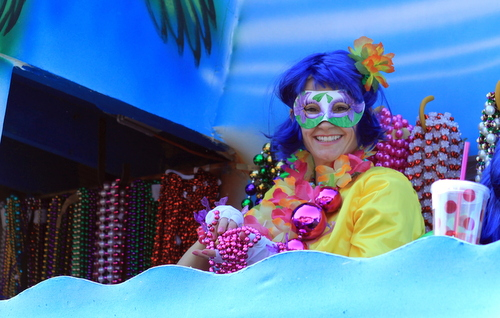 A member of the Krewe of Iris prepares to throw beads at the corner of St. Charles and Napoleon avenues. (Robert Morris, UptownMessenger.com)
