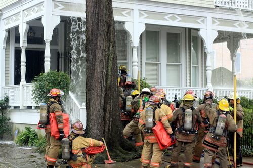 Firefighters prepare to enter a burning house at the corner of Philip and Chestnut streets in the Garden District on Tuesday afternoon. (Robert Morris, UptownMessenger.com)