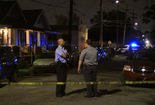 Two officers speak at the scene of a homicide in the 1300 block of General Ogden. (Robert Morris, UptownMessenger.com)