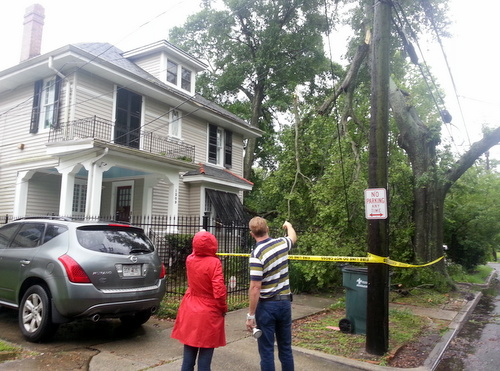 A homeowner in the 1200 block of Lowerline examines a power line pulled down by a falling tree branch in his front yard during Monday morning's storms. (Robert Morris, UptownMessenger.com)