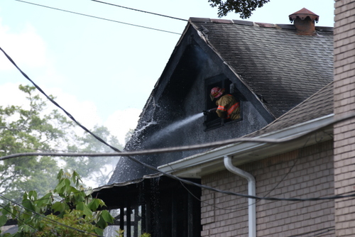 A firefighter battles the blaze at 5940 Freret Street. (Zach Brien for UptownMessenger.com)
