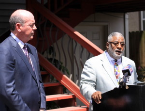 Attorney Michael Whitaker (left) listens as the Rev. Tom Watson describes damage to Watson Memorial Teaching Ministries on Napoleon Avenue during a news conference Wednesday morning. (Robert Morris, UptownMessenger.com)