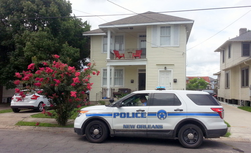 A NOPD officer guards a house where a man died of a gunshot that police say may have been self-inflicted. (Robert Morris, UptownMessenger.com)