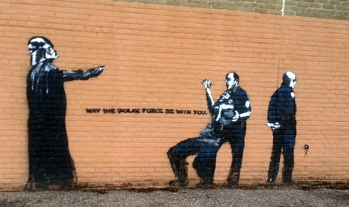 A politically-themed stencil on the side of the Priestley gym, by a street artist known as 'Az.' (Robert Morris, UptownMessenger.com)