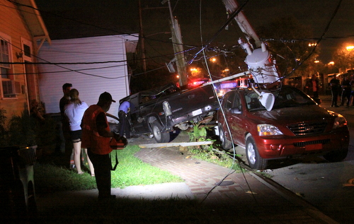 A downed utility pole lays across a pickup truck that is partially atop two other vehicles in the 4500 block of Tchoupitoulas Street on Friday night. (Robert Morris, UptownMessenger.com)