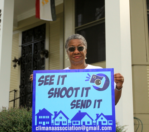 Rosalind Peychaud, immediate past president of the Climana Neighborhood Association, holds a sign encouraging her neighbors to email photos of local quality of life problems to the association. (Robert Morris, UptownMessenger.com)