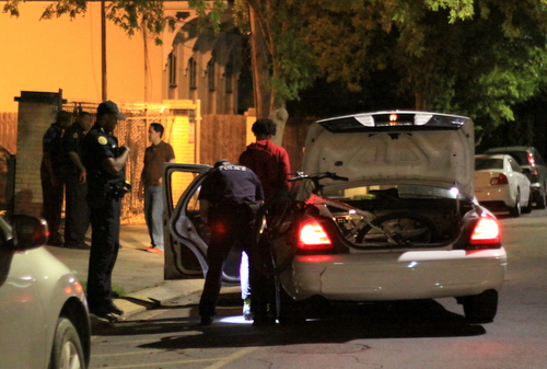 Police search a teen suspect arrested on a gun charge Friday night on Milan Street near St. Charles Avenue. (Robert Morris, UptownMessenger.com)