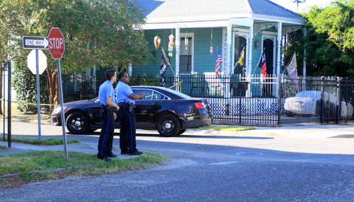 Two NOPD officers stand in the closed intersection of South Saratoga and General Taylor streets on Wednesday afternoon following what neighbors describe as a shooting. (Robert Morris, UptownMessenger.com)