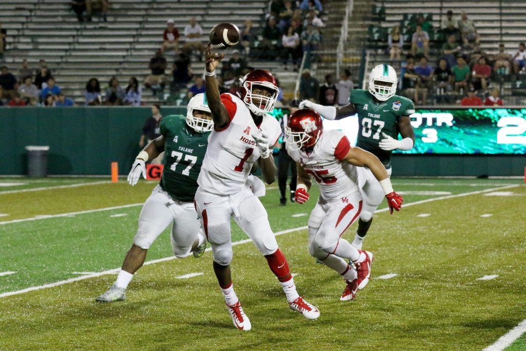 Greg Ward Jr., Houston quarterback, scrambles away from Tulane defensive tackle Tanzel Smart to complete a pass in the second half of Friday's game. Ward Jr. led the game in passing yards, rushing yards, passing touchdowns and rushing touchdowns.
