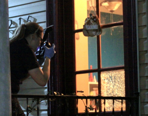 New Orleans Police Department crime-scene technician Traci Ban photographs a bullet hole through a window pane in the front door of a Robert Street home on Tuesday evening. (Robert Morris, UptownMessenger.com)