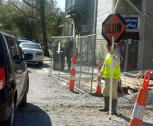 A construction worker guides a passing SUV across Prytania Street on Friday morning. (Robert Morris, UptownMessenger.com)