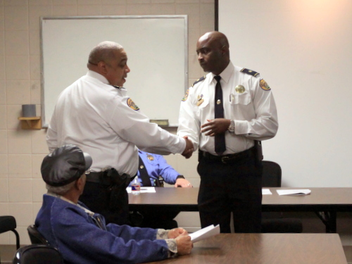 NOPD Superintendent Michael Harrison (left) congratulates new Second District Commander Shaun Ferguson with a handshake during a community meeting this week at Touro Infirmary. (Robert Morris, UptownMessenger.com)