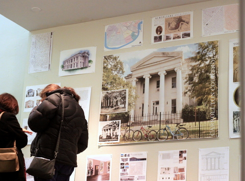 Two attendees at Thursday's presentation on the Carrollton Courthouse at Tulane University examine plans and documents produced by architecture students. (Robert Morris, UptownMessenger.com)