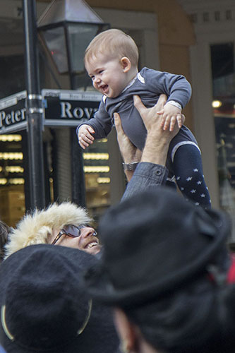 A man plays with child on the corner of St. Peter and Royal in the French Quarter before the David Bowie parade. On Saturday, the Preservation Hall Jazz Band and members of Arcade Fire led a second line through the French Quarter in honor of musician David Bowie who died on January 10, 2016.