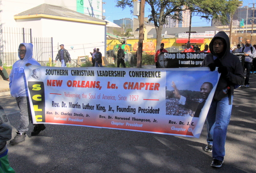 Marchers carry a banner describing the history of the founding of King's Southern Christian Leadership Conference in New Orleans. (Robert Morris, UptownMessenger.com)