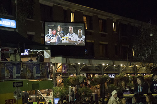 """Superior Grill, near the corner of St. Charles avenue and Amelia street, projected the Super Bowl onto a screen so people at Bacchus would not miss the game. Bacchus 2016 rolled with the theme """"Flights of Delight."""" (Zach Brien, UptownMessenger.com)"""