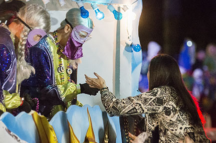 """A rider on the """"Bacchanahoppa"""" float gives beads to an eager attendee. Bacchus 2016 rolled with the theme """"Flights of Delight."""" (Zach Brien, UptownMessenger.com)"""