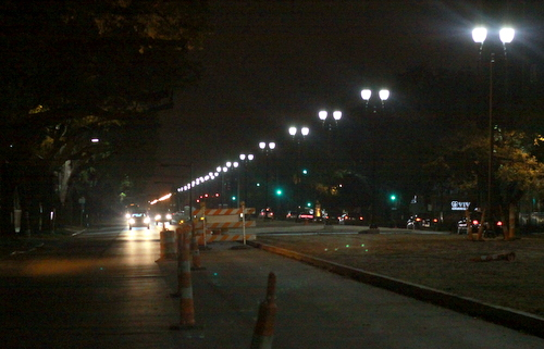 A row of new street lights and two lanes of traffic on Napoleon Avenue can be seen approaching Freret Street on the evening of March 31. Construction on this section will be finished in April, and on the entire avenue by the end of the year, officials said. (Robert Morris, UptownMessenger.com)