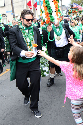 A member of the Irish Channel St. Patrick's Day club hands out a flower during the 66th annual Irish Channel St. Patrick's Day parade on Magazine St. on Saturday, March 12.  (Zach Brien, UptownMessenger.com)