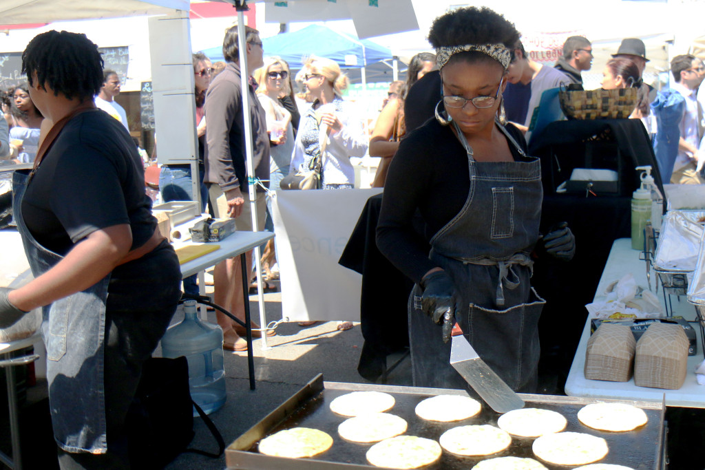 Aileron Angelin prepares food at the Black Swan Food Experience tent at the 2016 Freret Street Festival. The event featured 18 artists on three stages, 35 food vendors and craft vendors ranging from Freret and Soniat to Napoleon Avenue. (Zach Brien, UptownMessenger.com)