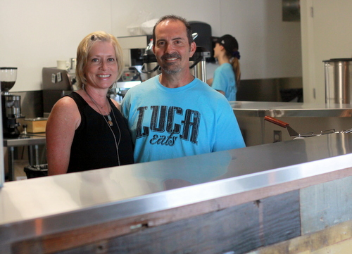 Ellen and Darryl Cortello stand behind a counter made of salvaged wood at Luca Eats. (Robert Morris, UptownMessenger.com)