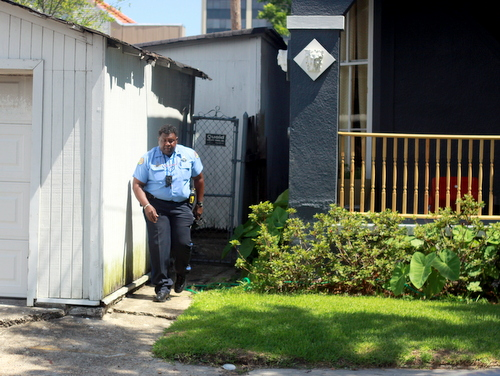 A police officer emerges from the side of a house on LaSalle Street after a man was shot there Thursday morning. (Robert Morris, UptownMessenger.com)