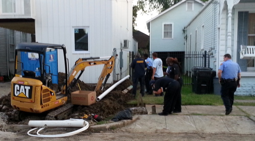 Crime-scene investigators photograph what witnesses described as a human jaw bone outside a home-construction site on Zimpel Street on Tuesday. (Robert Morris, UptownMessenger.com)