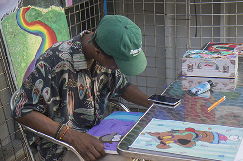 Da'Roll Mitchell paints some artwork at his booth at Roux Carre during First Fridays on the Boulevard on July 1. The event highlighted businesses on Oretha Castle Haley and included drink and food specials, art exhibits and live music.
