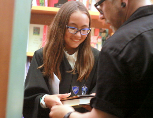 "Sisira Holbrook, first in line for the midnight release of ""Harry Potter and the Cursed Child,"" smiles in anticipation as Octavia employee James Wilson hands her a copy of the book. (Robert Morris, UptownMessenger.com)"