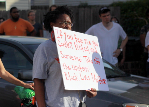 A protester holds a sign during a rally demanding justice for Eric Harris on Friday, July 8. (UptownMessenger.com file photo)