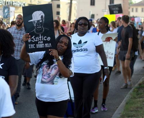 The mother of Eric Harris, who was shot to death Feb. 8 by Jefferson Parish deputies, marches with a sign demanding justice for her son following a rally in Central City on Friday. (Robert Morris, UptownMessenger.com)