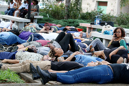 "People partake in a ""die-in"" in front of NOPD headquarters. The event drew dozens of participants who laid face-down on the ground to stand in solidarity with those who have lost their lives at the hands of police officers. (Zach Brien, UptownMessenger.com)"
