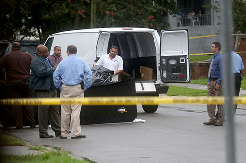 Workers from the coroners office load a body into after a fatal shooting in the 2200 block of Peniston street uptown on Thursday. (Zach Brien, UptownMessenger.com)