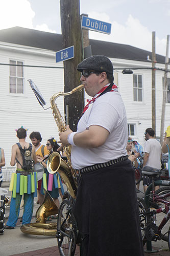 """Chris Freire of the Browncoat Brass practices his saxophone before the parade rolls. The Krewe of O.A.K. celebrated the 30th anniversary of Mid Summer Mardi Gras with the theme """"Get Wet"""". (Zach Brien, UptownMessenger.com)"""