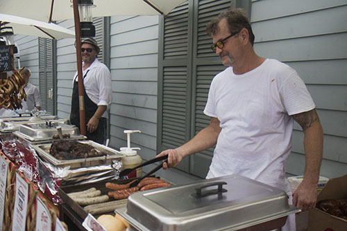 """Greg James, left, of Bratz Y'all, prepares some food before the parade rolls. The Krewe of O.A.K. celebrated the 30th anniversary of Mid Summer Mardi Gras with the theme """"Get Wet"""". (Zach Brien, UptownMessenger.com)"""