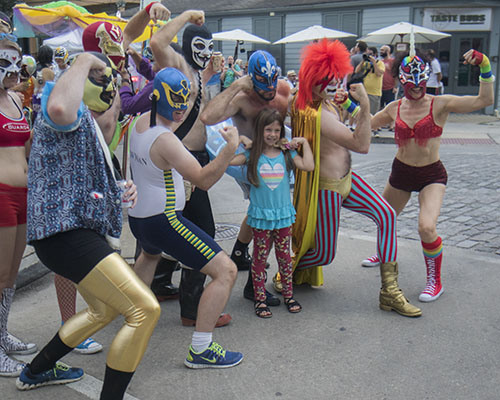 """Vivian O'Brien flexes with members of El Lucha on Oak street before the parade. The Krewe of O.A.K. celebrated the 30th anniversary of Mid Summer Mardi Gras with the theme """"Get Wet"""". (Zach Brien, UptownMessenger.com)"""