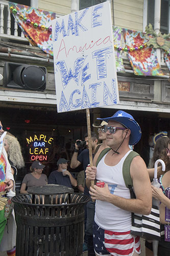 """Dustin Cook holds up a """"Make America Wet Again"""" sign outside of the Maple Leaf Bar. The Krewe of O.A.K. celebrated the 30th anniversary of Mid Summer Mardi Gras with the theme """"Get Wet"""". (Zach Brien, UptownMessenger.com)"""