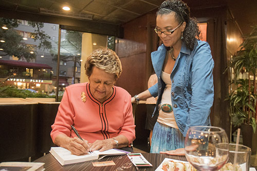 Sybil Morial, left, signs a copy of her book, Witness to Change) for Lishunda Franklin, right. Morial read selections from her book and signed copies at Poseidon restaurant on Saint Charles avenue. (Zach Brien, UptownMessenger.com)