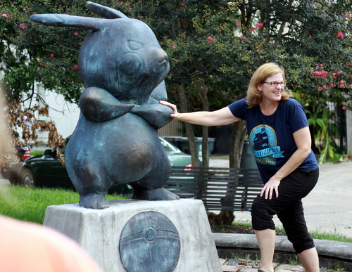 A visitor to Terpsichore Street poses with the mysterious new Pikachu statue on Monday morning. (Robert Morris, UptownMessenger.com)