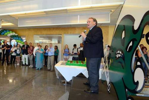 "Tulane University president Michael Fitts stands in front of a new ""Angry Wave"" rendering as he celebrates the reopening of the university's Lavin-Bernick Center food court with new offerings. (courtesy photo)"