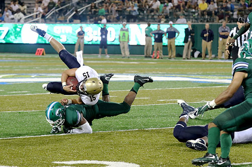 Tulane linebacker Nico Marly upends Navy quarterback Will Worth. Navy defeated Tulane 21-14 at Yulman Stadium. (Zach Brien, UptownMessenger.com)